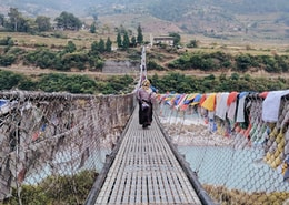 person walking on bridge with clothes hanging