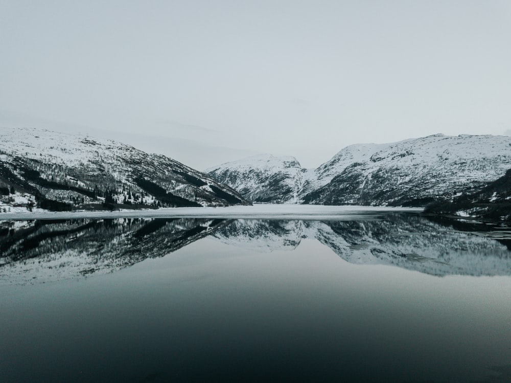 snow covered mountain and body of water