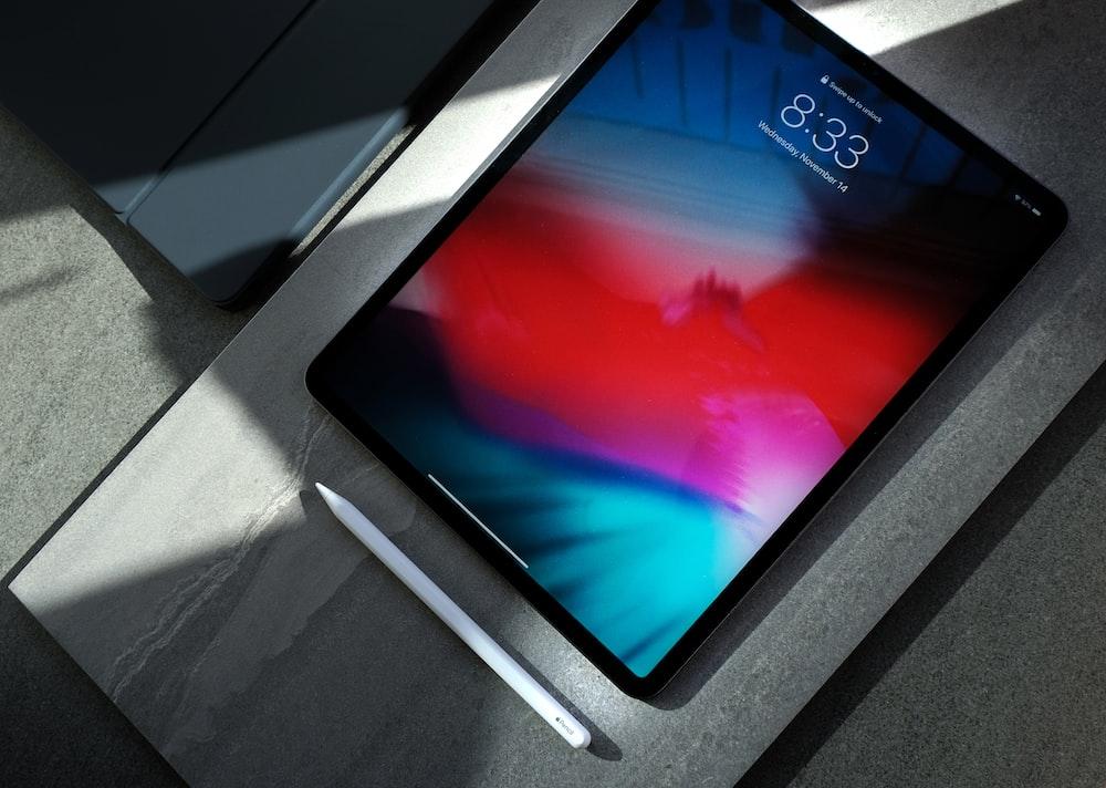 black iPad with white stylus pen