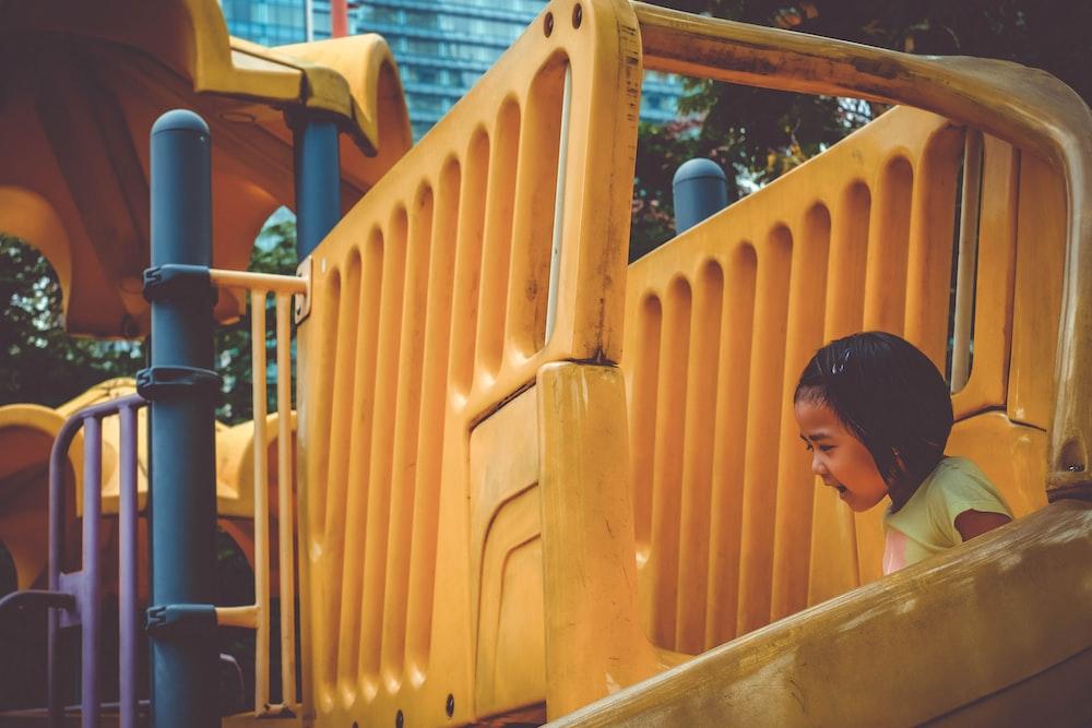 girl playing on yellow slide during daytime