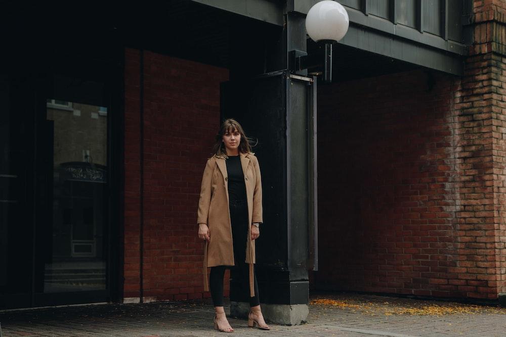 woman in brown trench coat stands in front of glass door