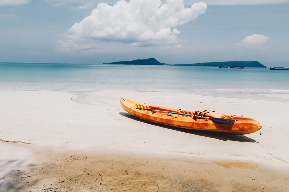 yellow and black kayak boat on seashore
