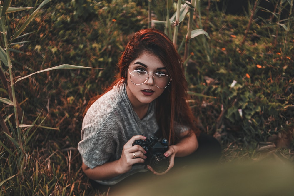 woman holding camera while sitting on grass
