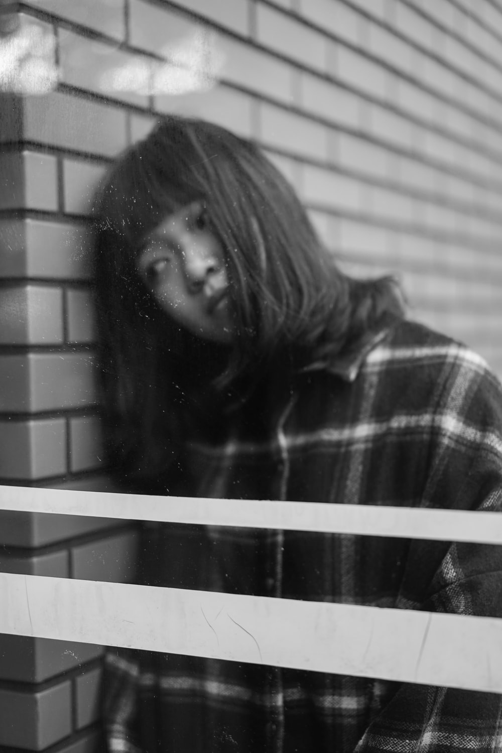 grayscale photography of woman leaning on brick wall