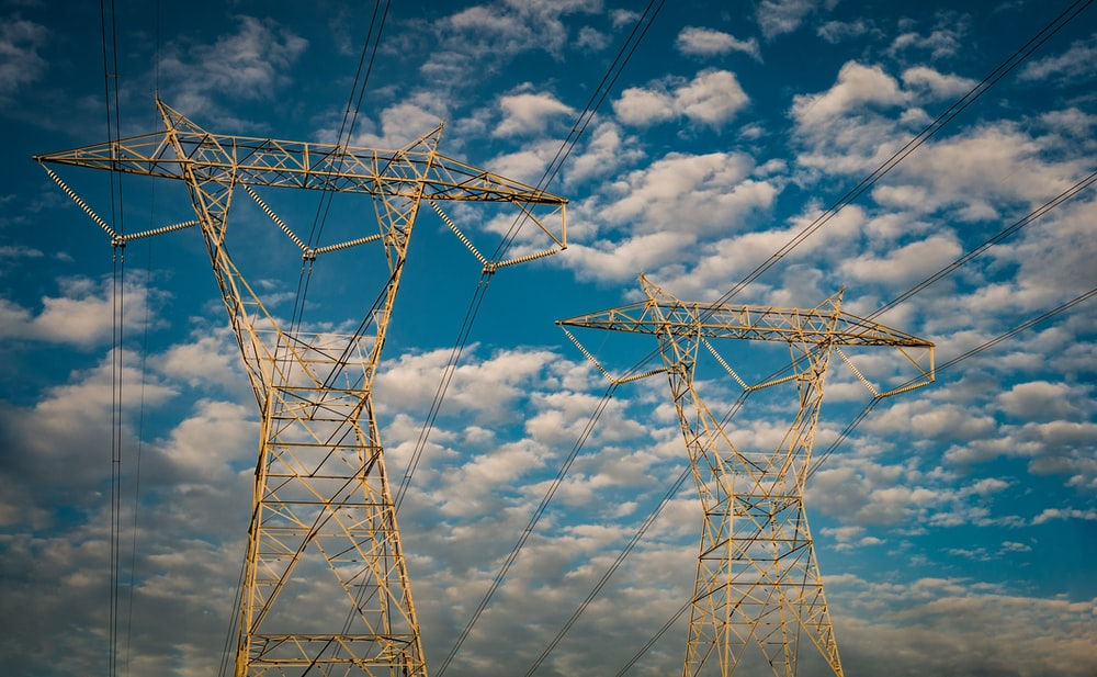 two white metal electric towers under blue sky
