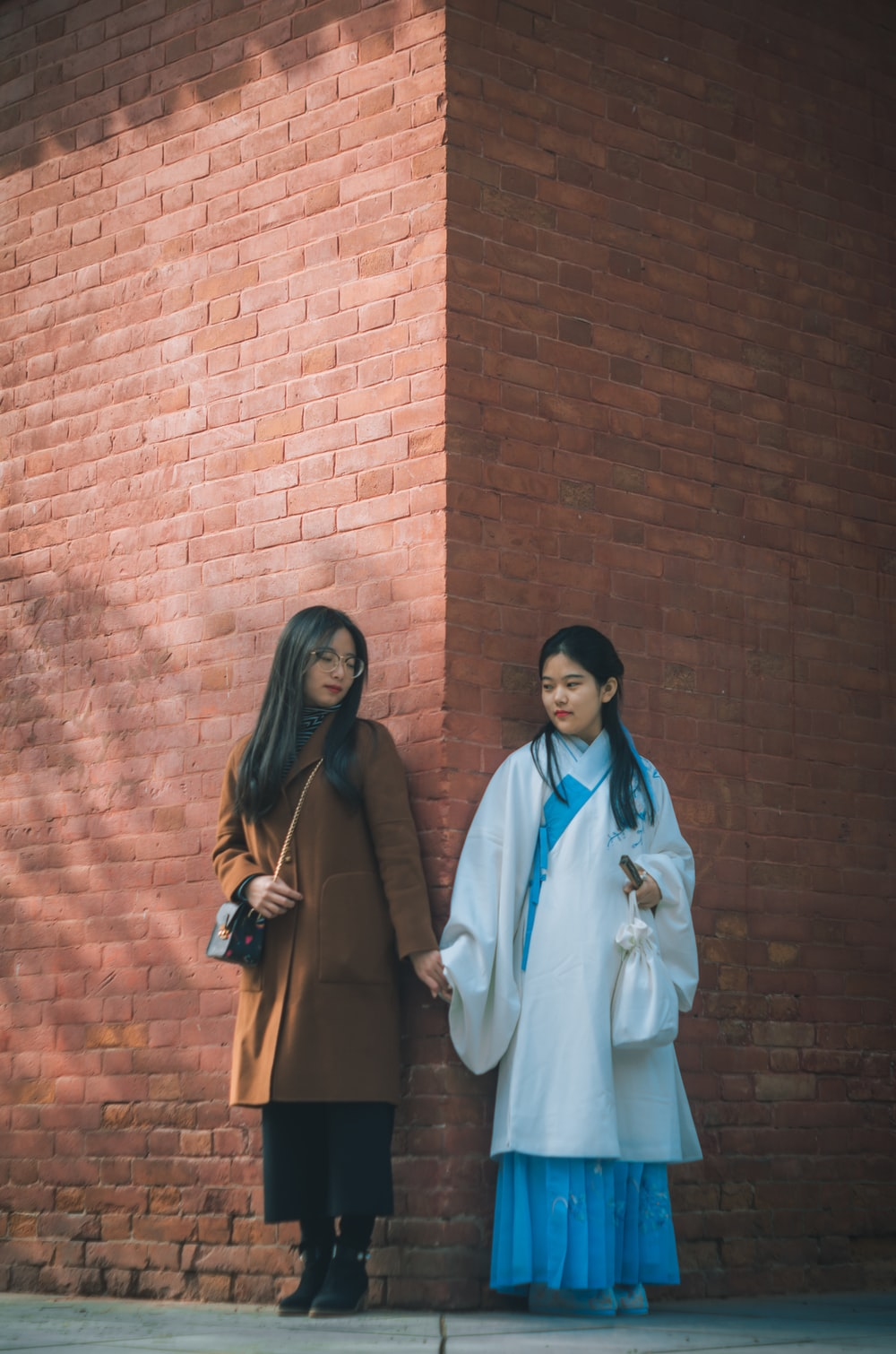 two women holding hands near wall