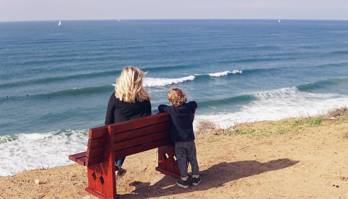 niño y madre mirando las olas