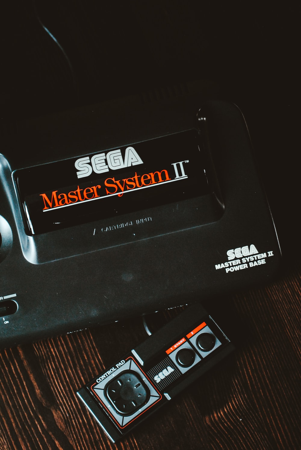 black Sega Master System II device on brown wooden surface