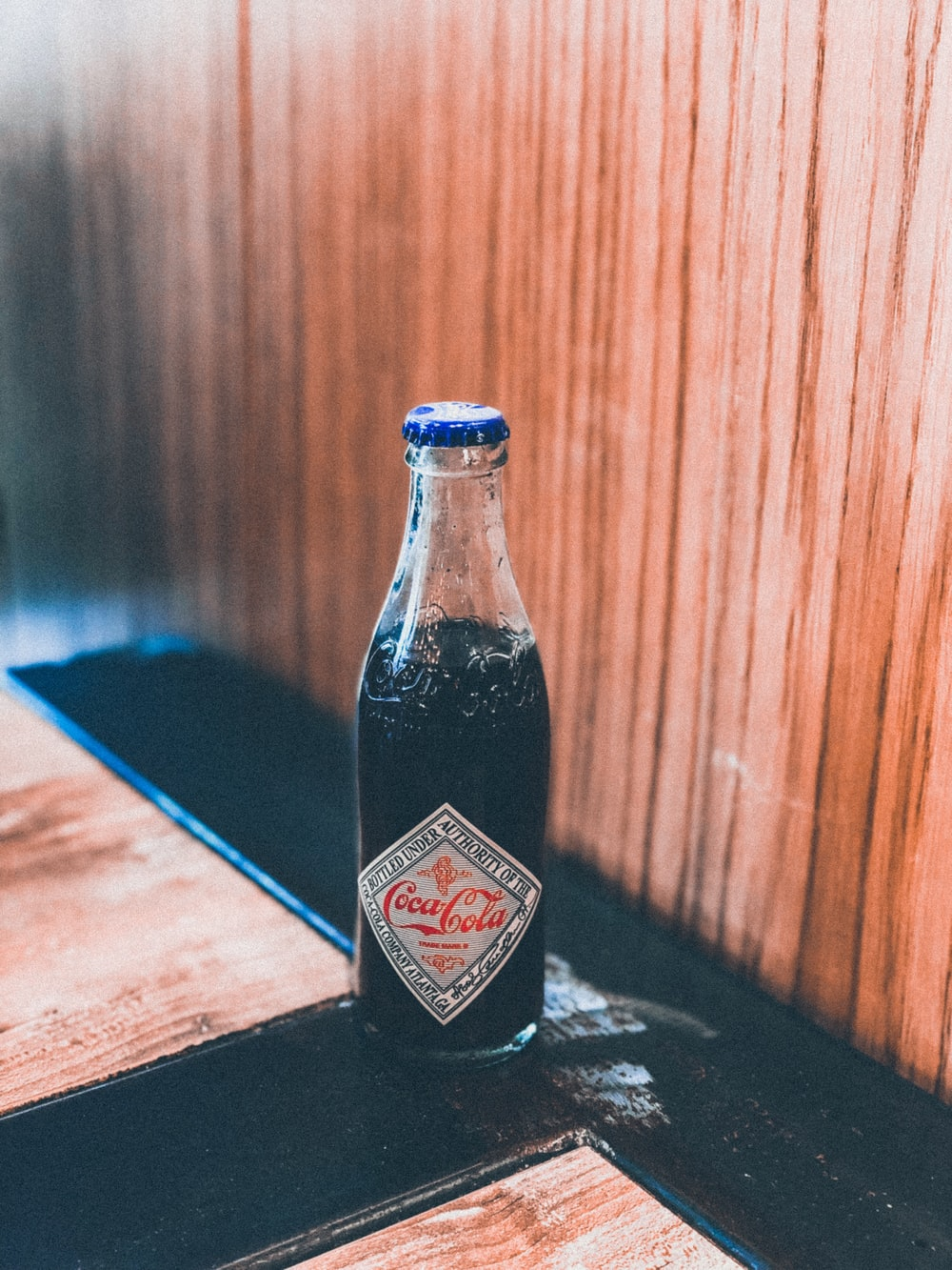 Coca-Cola bottle on brown and black surface