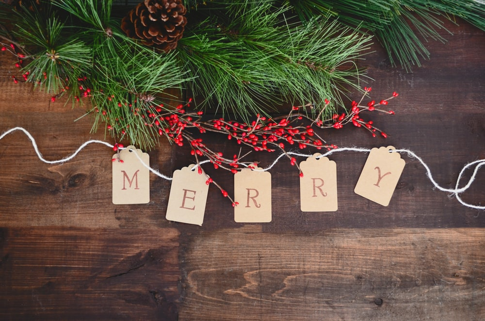MERRY text cutout on white string by wreath