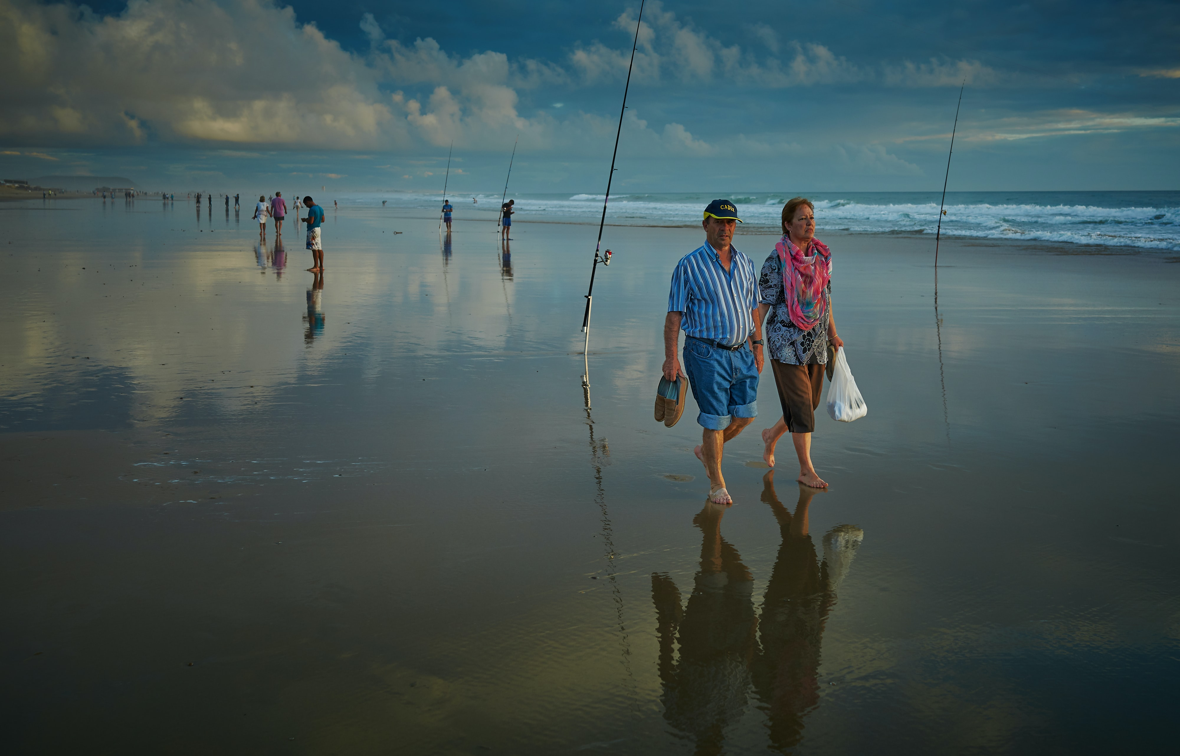 two man and woman walking on seashore