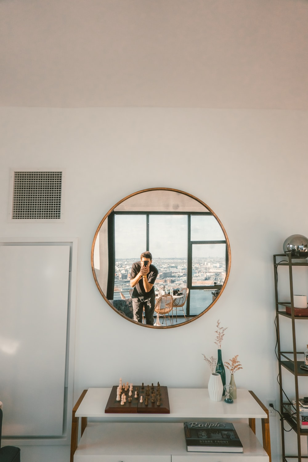 person taking photo of round wall mirror during daytime