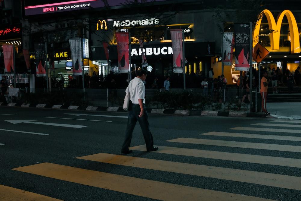 man in white shirt walking on pedestrian lane
