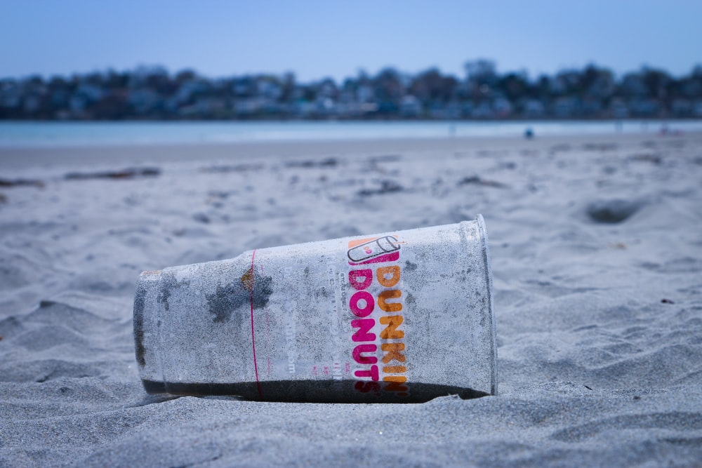 Dunkin Donut disposable cup on the sand