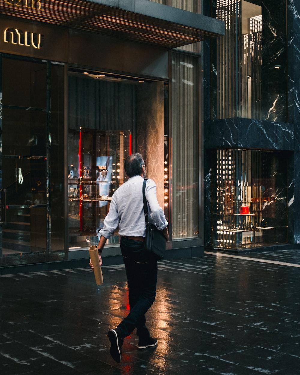 man holding brown tube walking on sidewalk