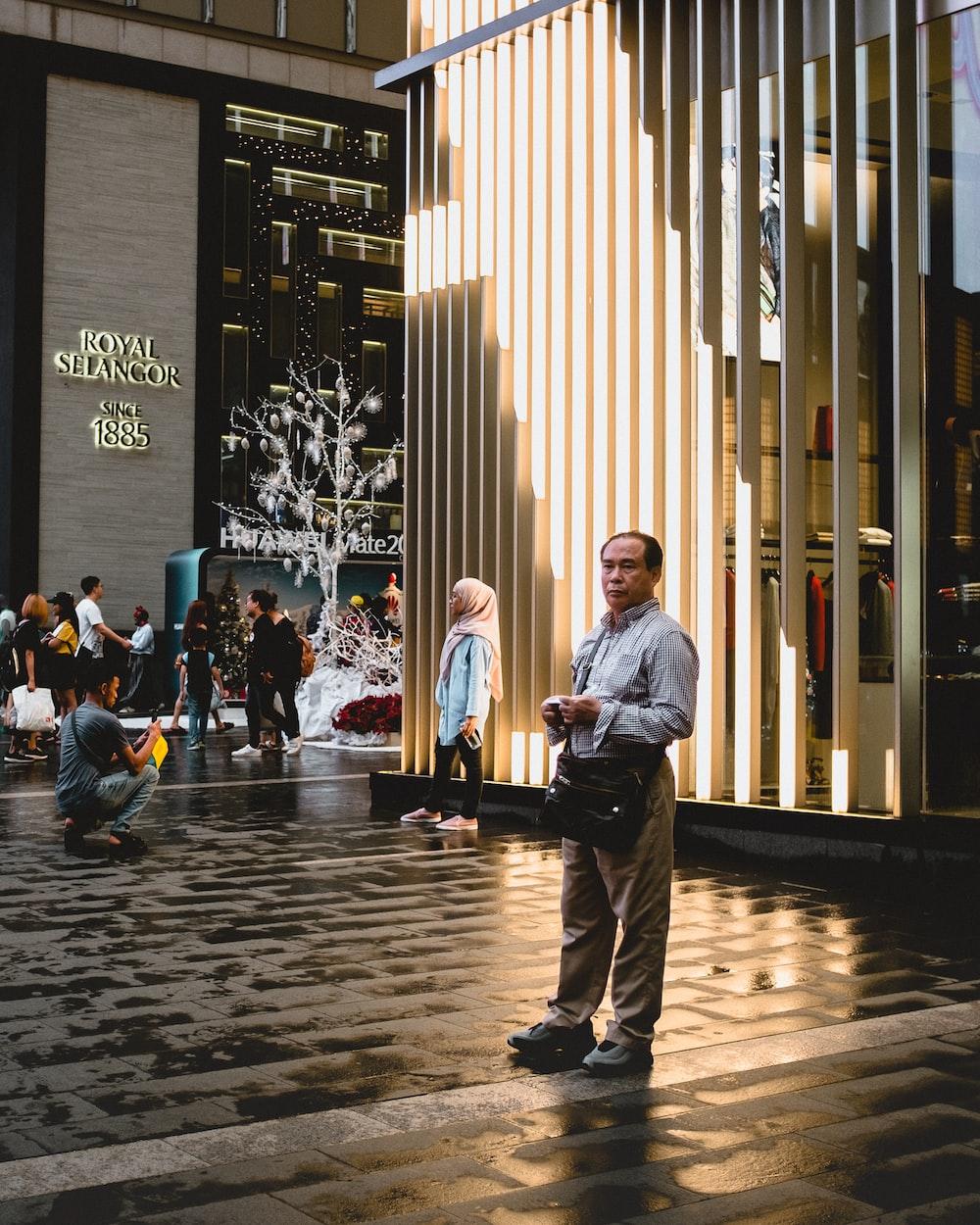 man in grey dress shirt and beige pants near people walking