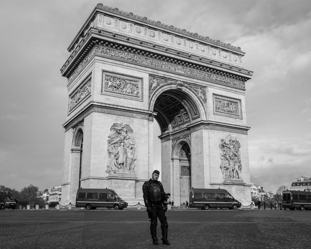 grayscale photography of man standing near Arc de Triomph