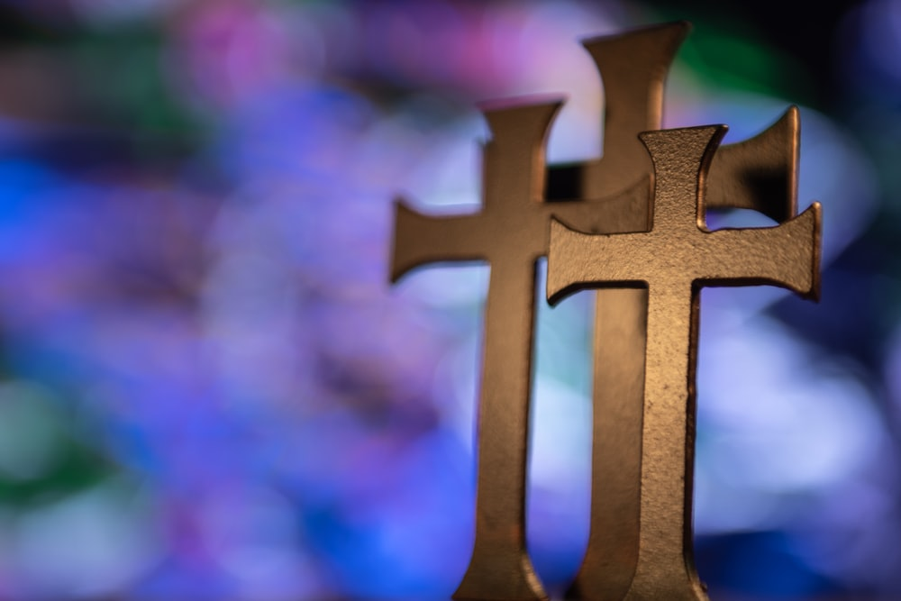 several gold-colored cross table decors in selective focus photography