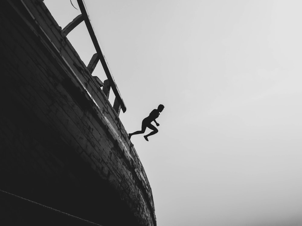 silhouette photography of person jumping on sailing ship