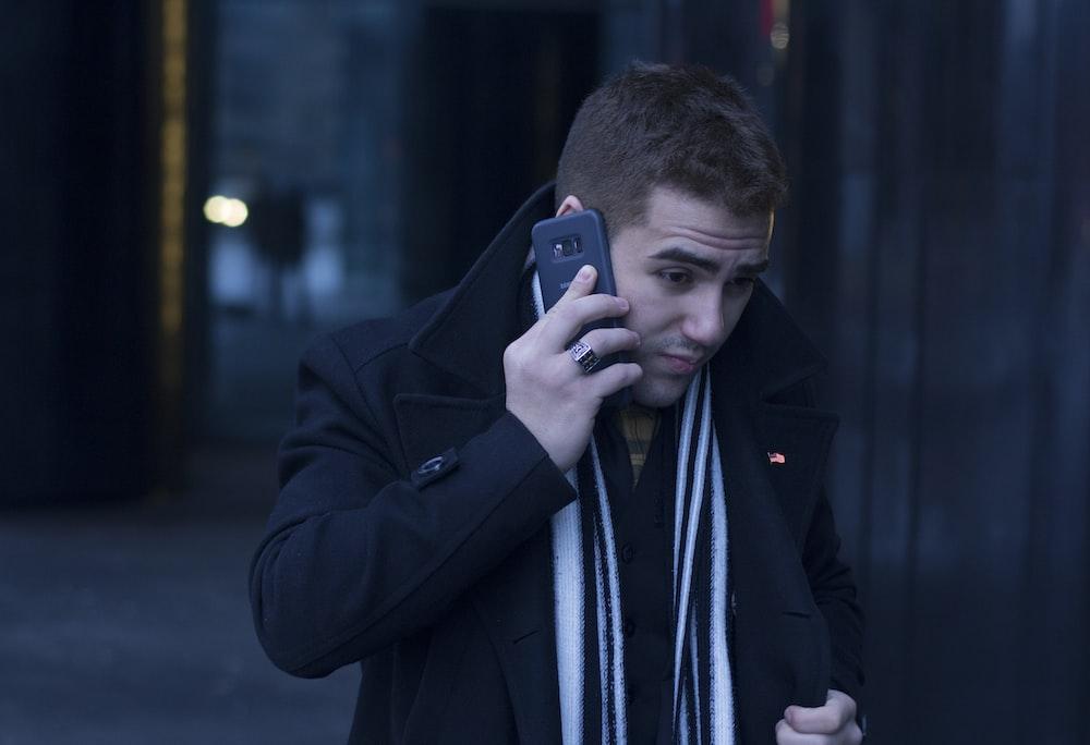 man holding smartphone wearing black suit jacket