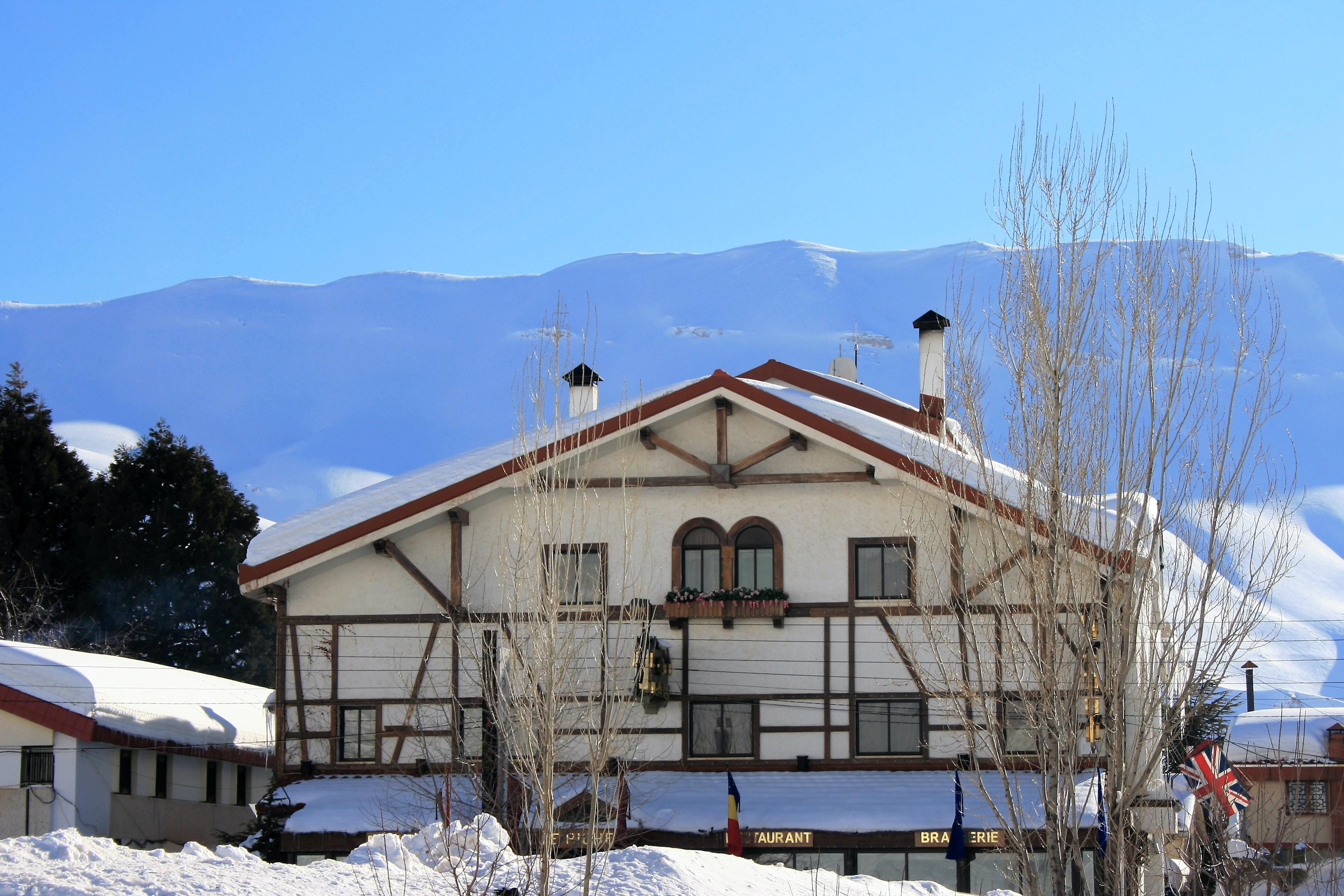 white and black concrete house near mountain during daytime