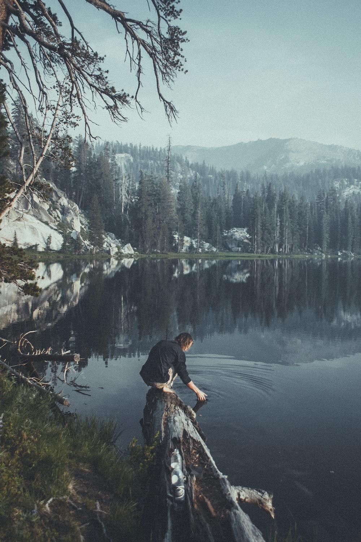 man on wood log beside water