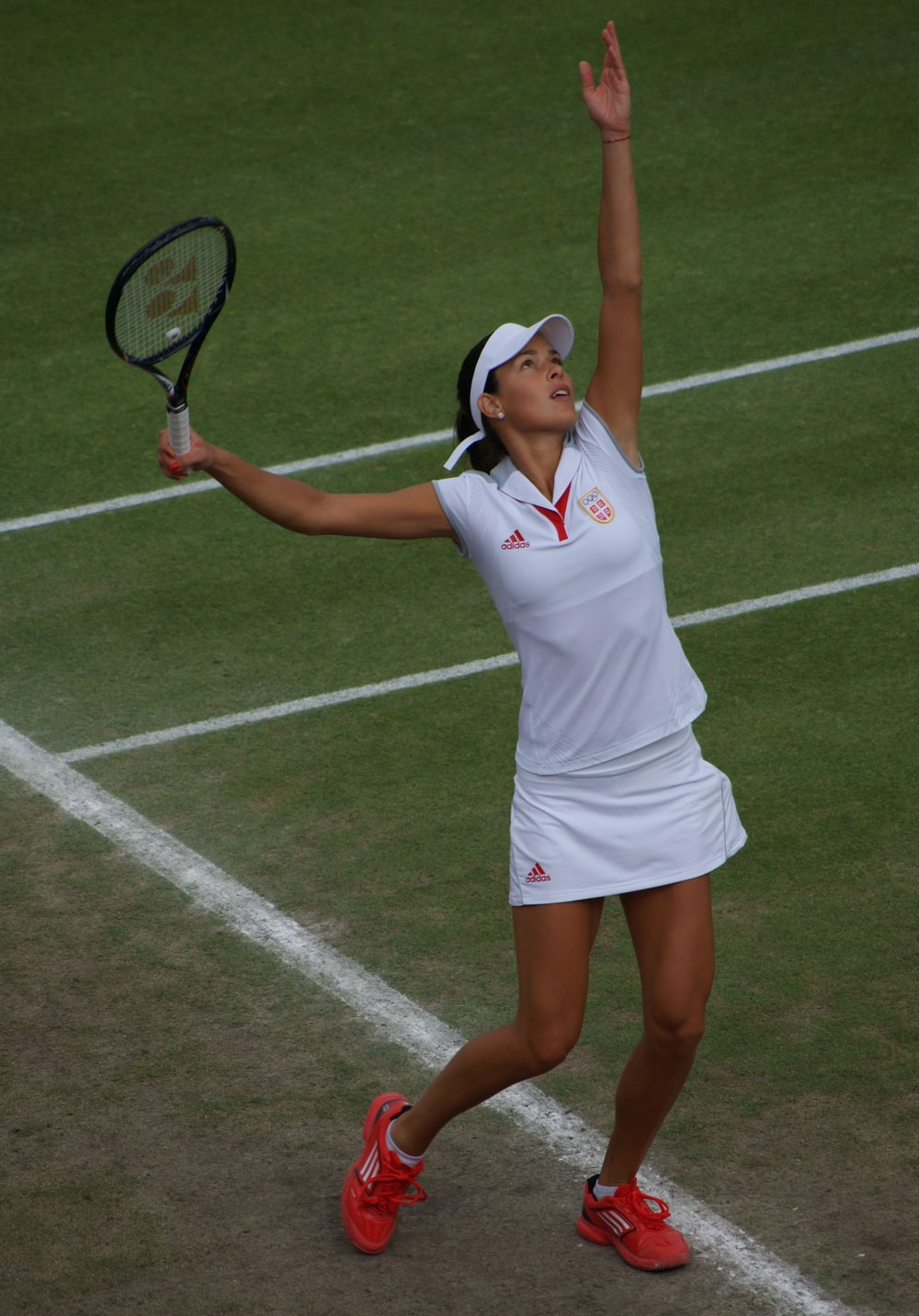 woman playing tennis about to hit tennis ball