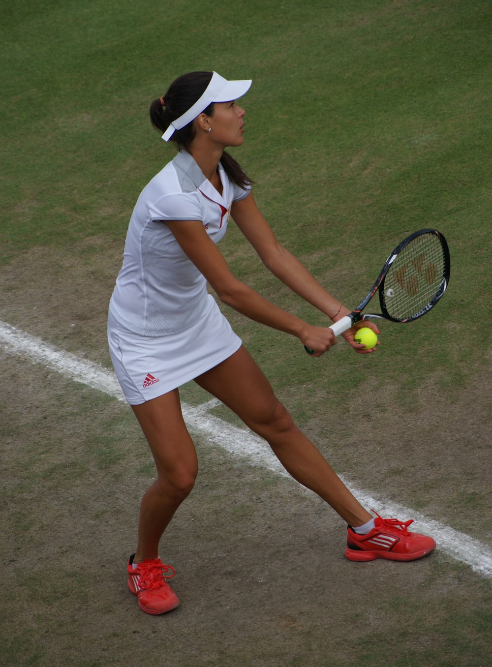 woman holding tennis racket and ball
