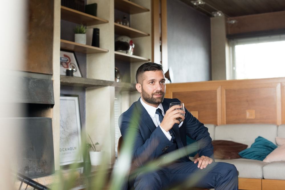 man in blue suit holding cup
