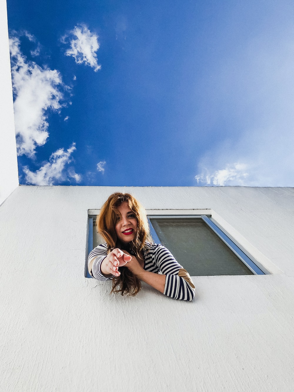woman on window reaching her hands down under blue sky
