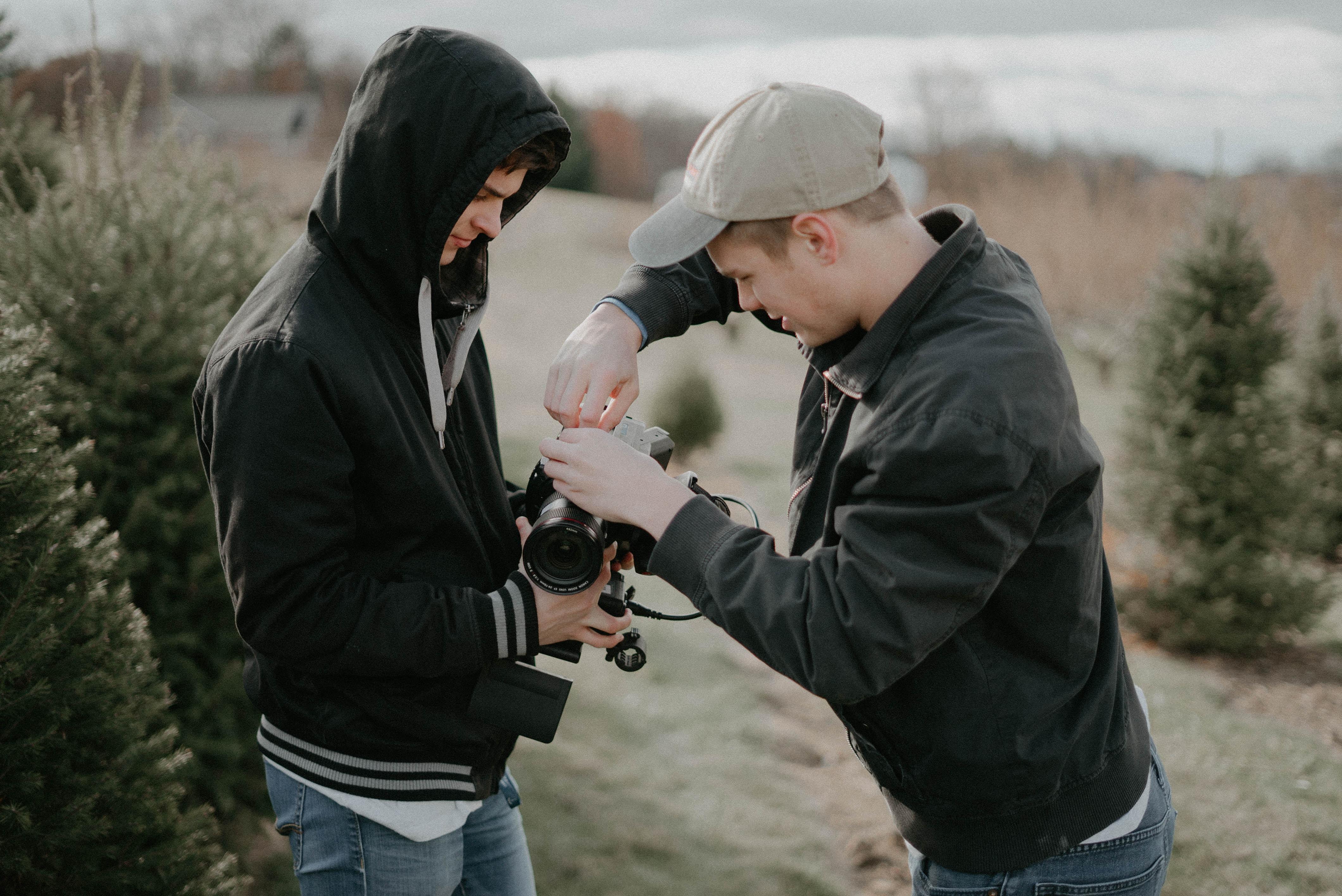 man fixing DSLR camera while man holding