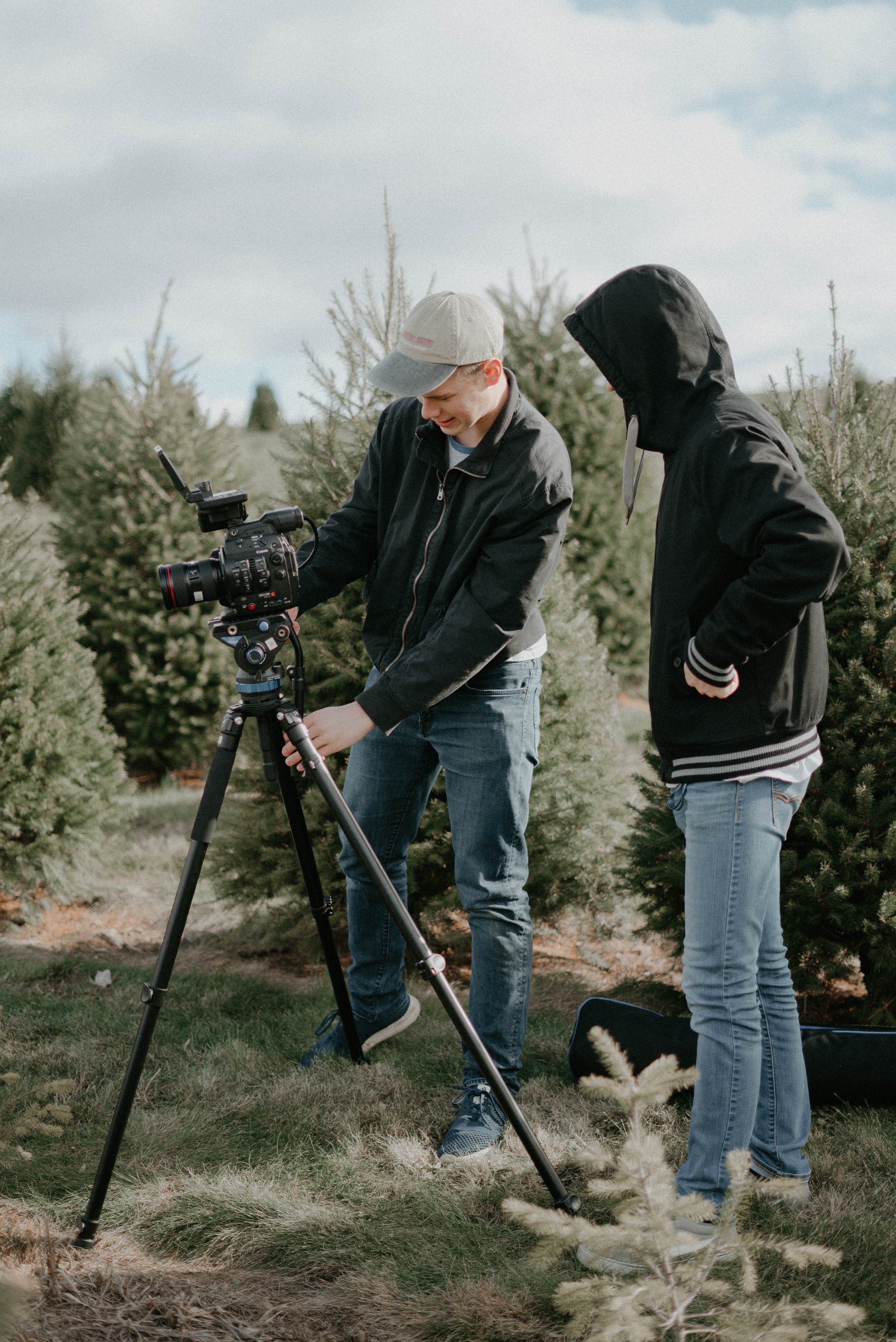 two people standing near camera with tripod