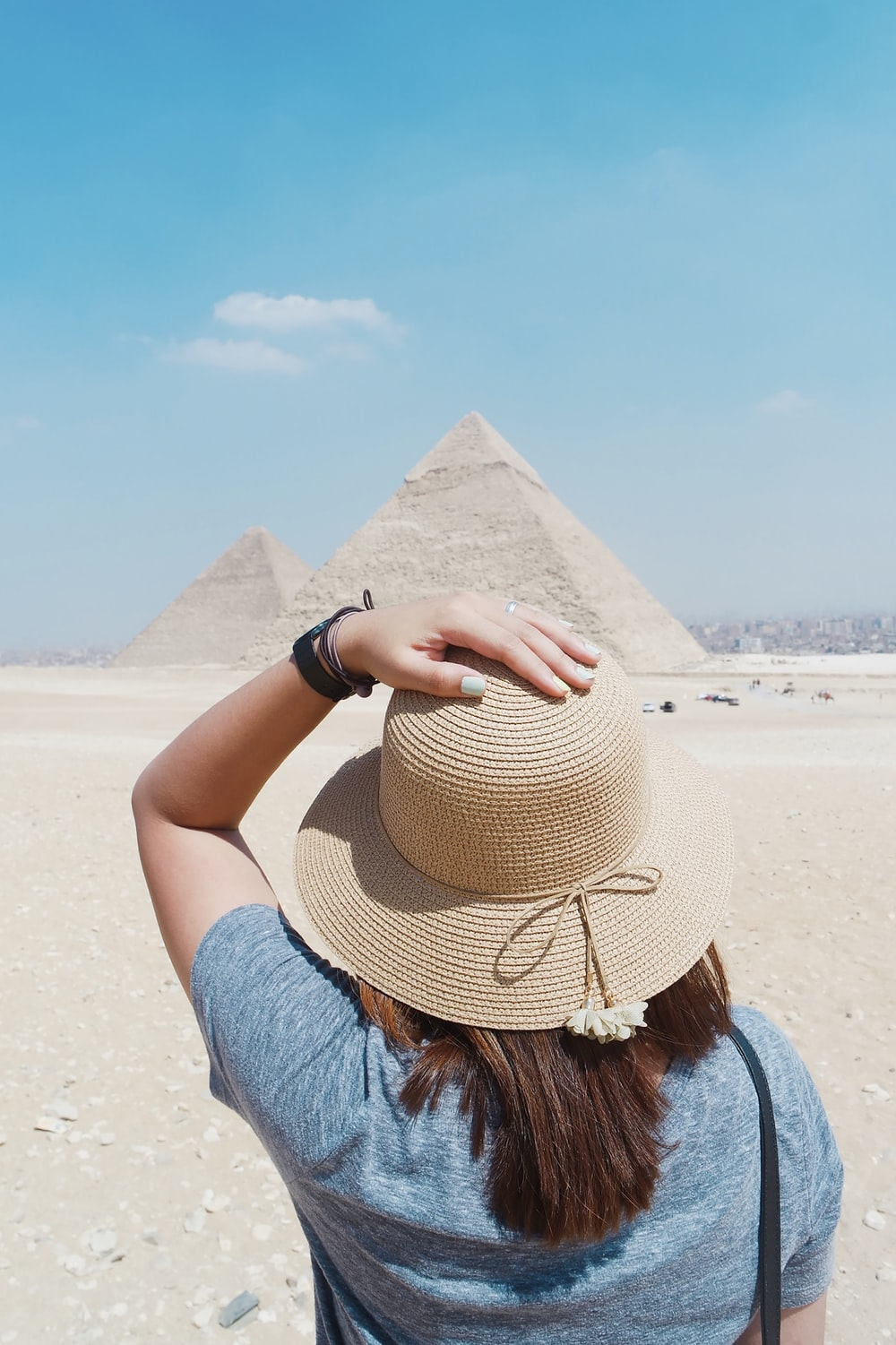 woman in blue top standing in front of Pyramid during daytime