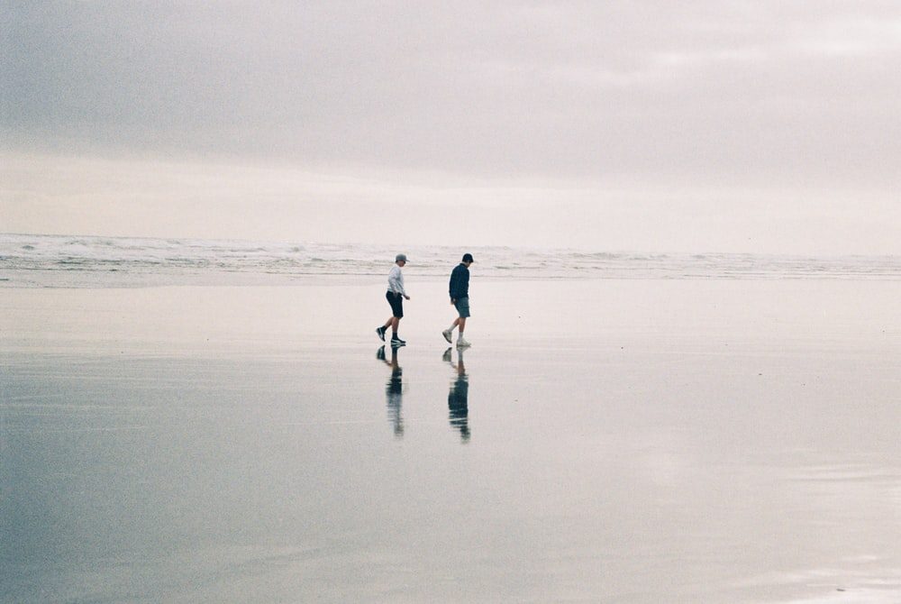 two person walking at beach during daytime
