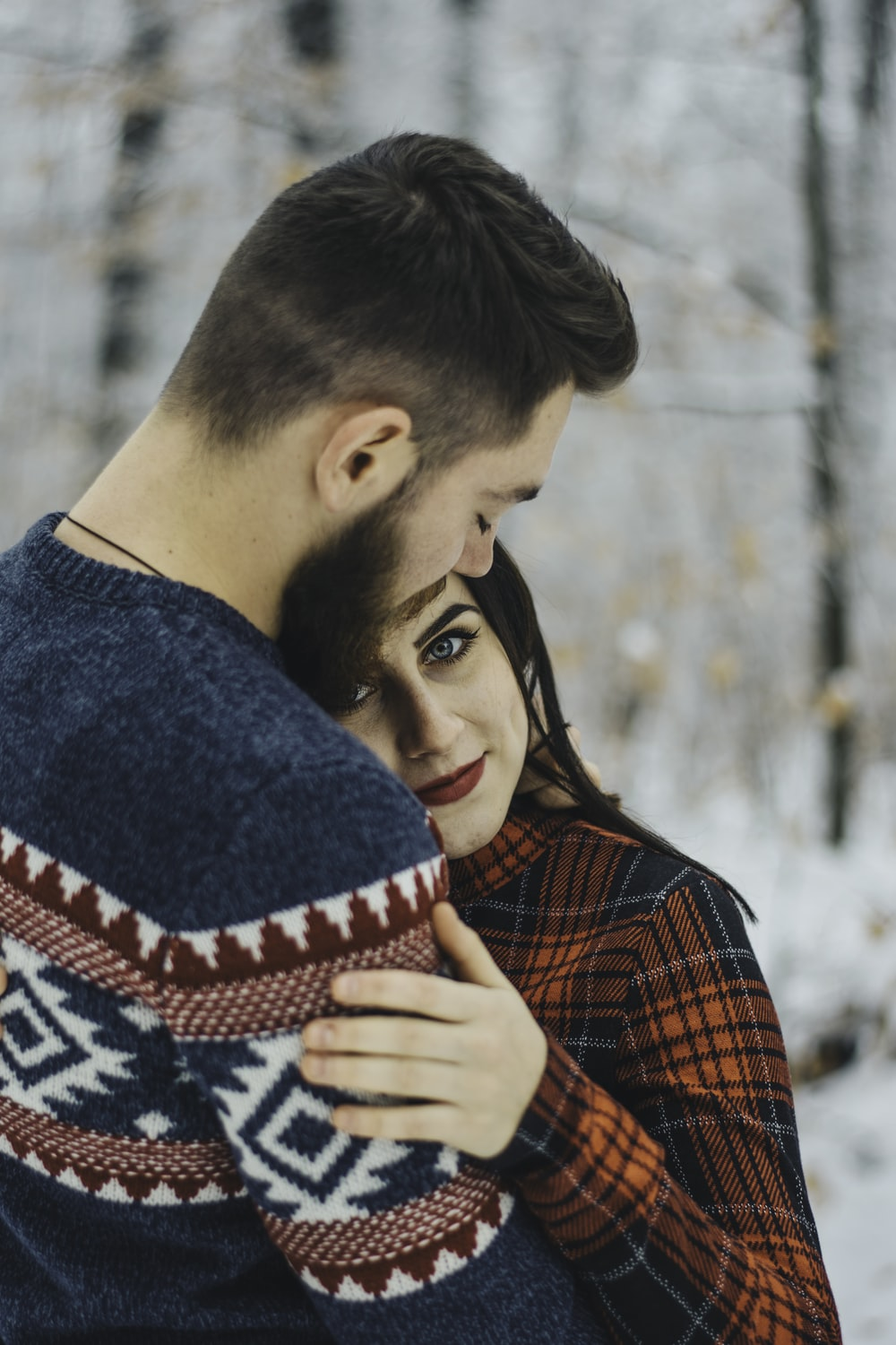 man and woman hugging outdoors
