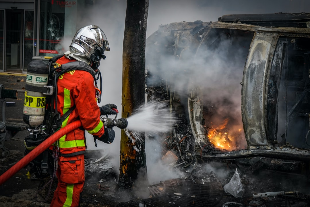 Fire fighter splashed water on a burned car by yellow vest protesters. Thousands of riot police continue to clash with protesters in the nation's worst urban riots in decades, Paris, France, Saturday, Dec. 8, 2018.