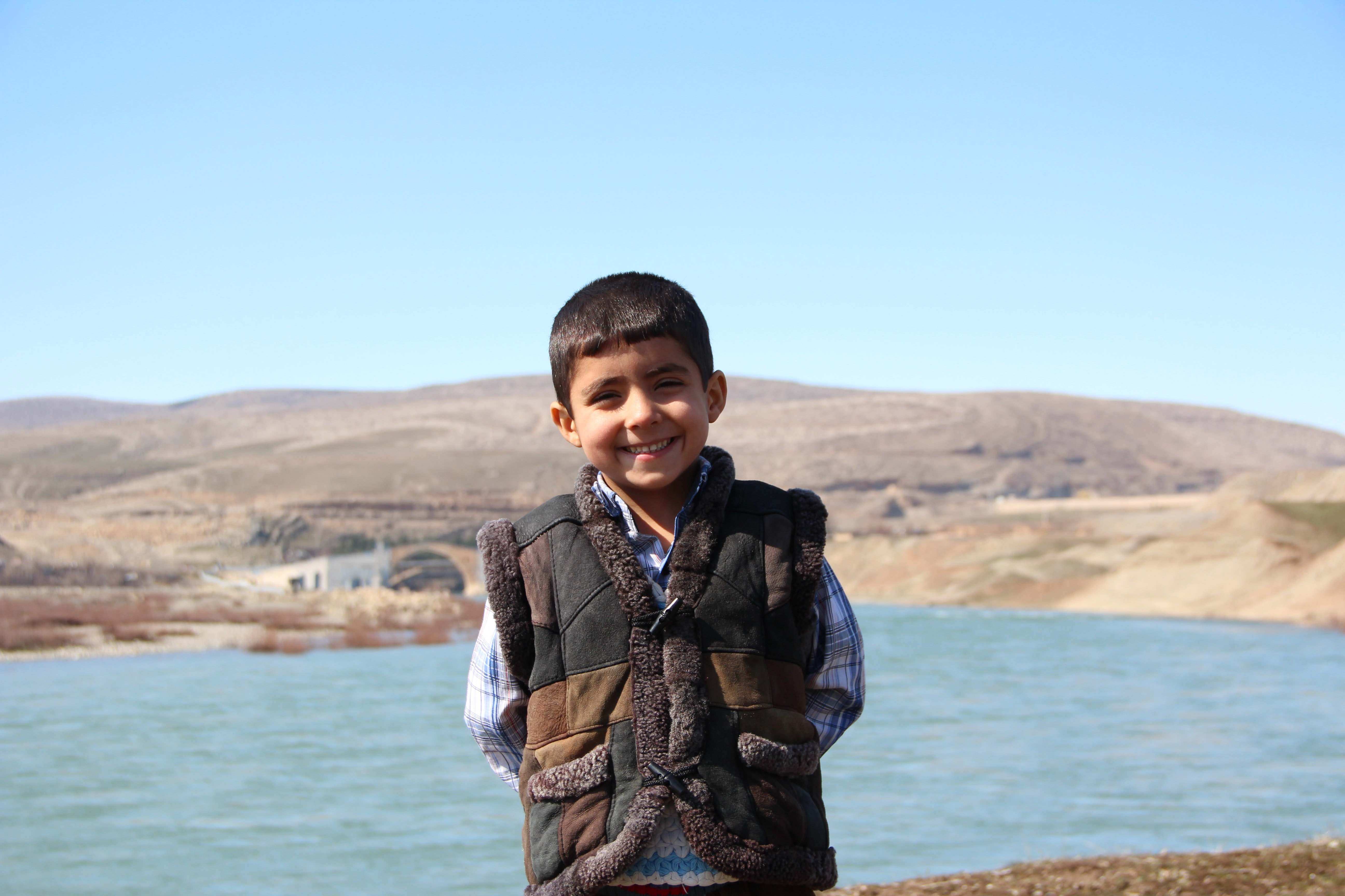 boy standing in front of body of water