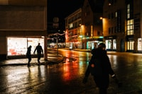 man walking along wet road of city during nighttime