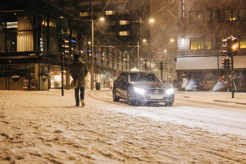 few people walking near road beside vehicle and snow falling down