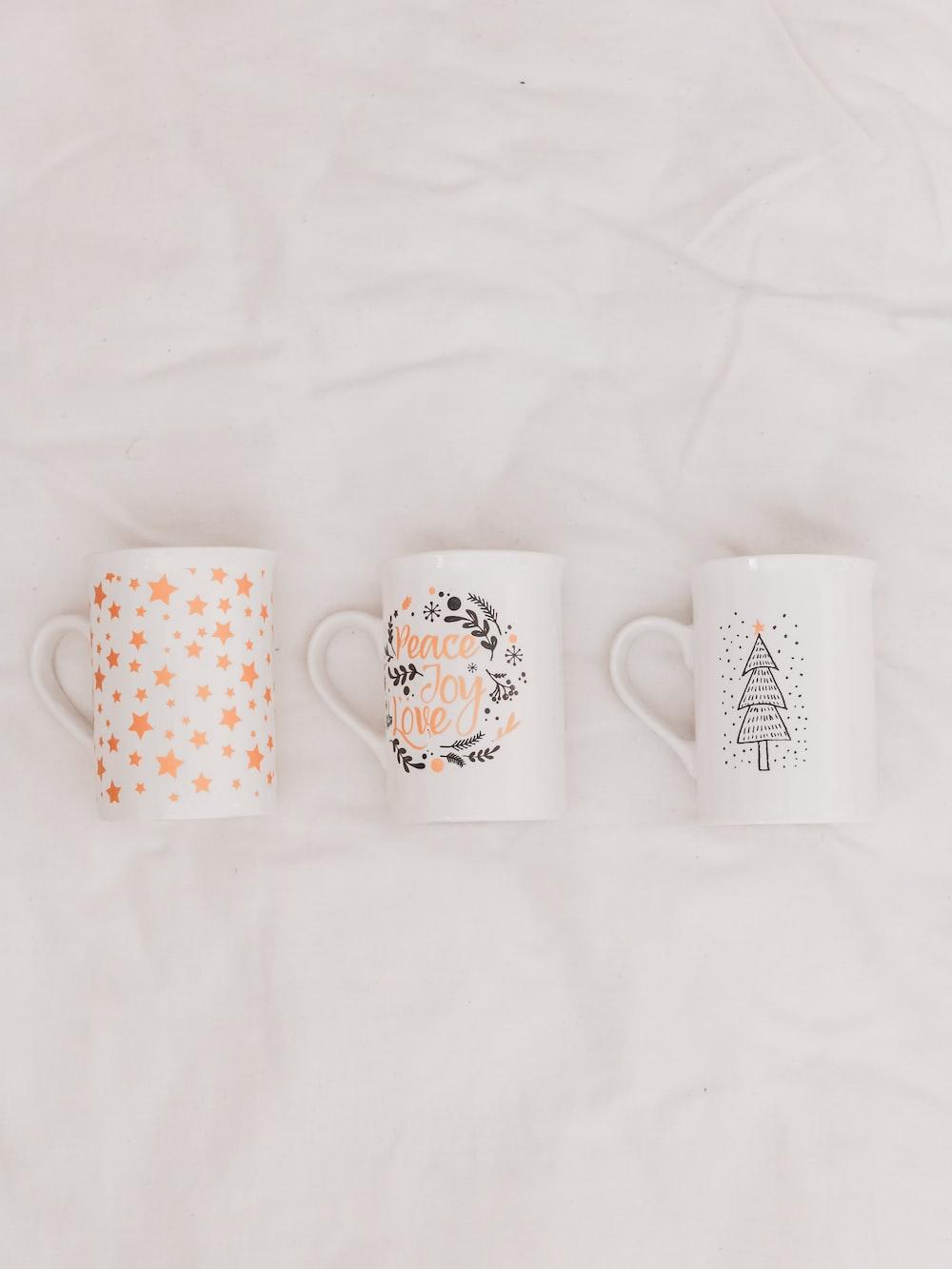 three white-and-multicolored ceramic mugs on white textile