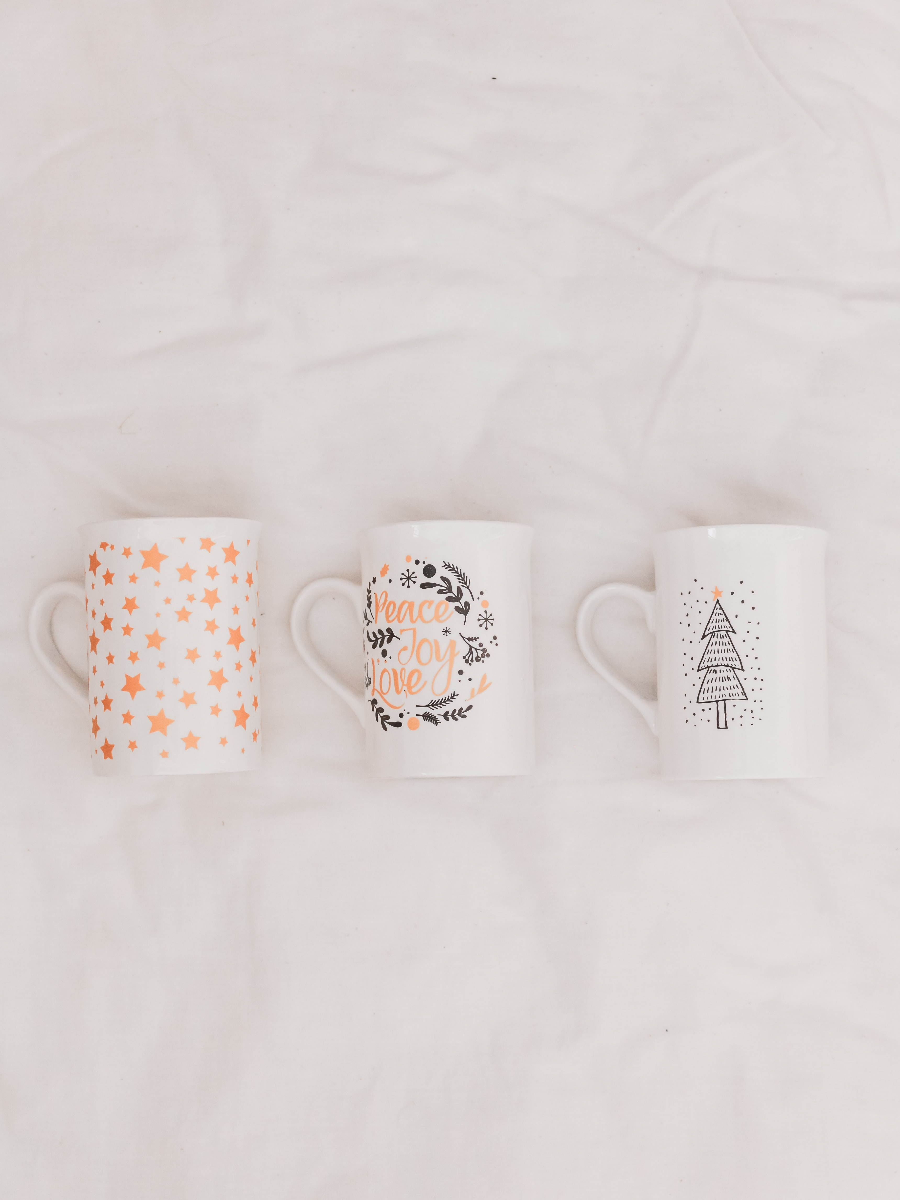 two white and pink floral ceramic mugs