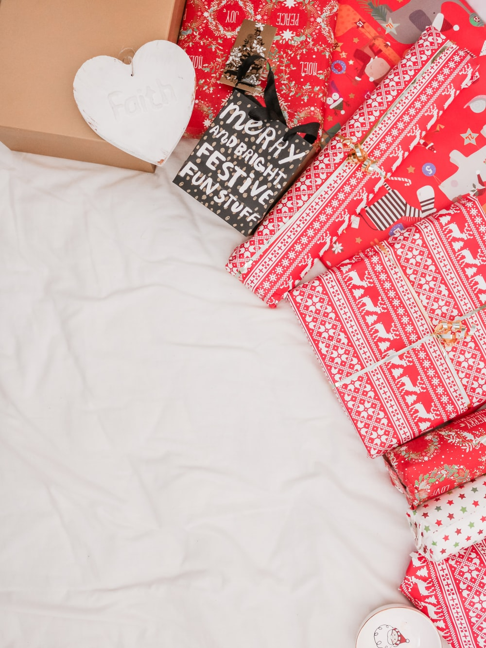 red and black packed presents on white textile