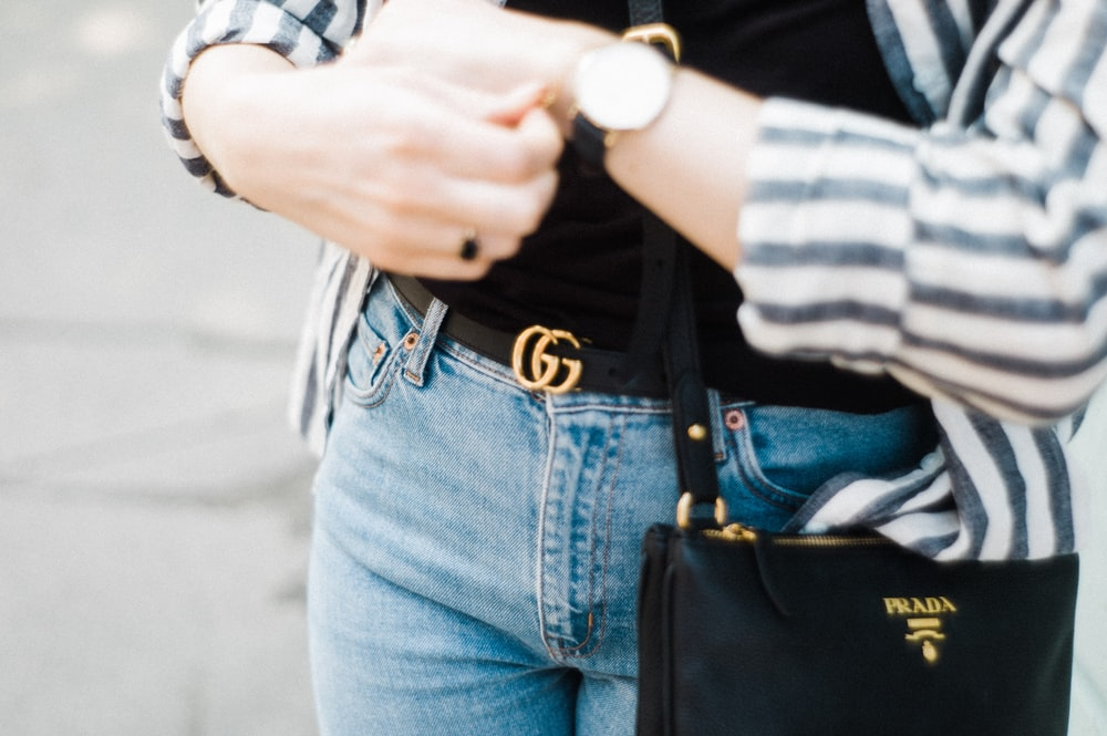woman wearing cardigan and denim bottoms looking at the time on her watch