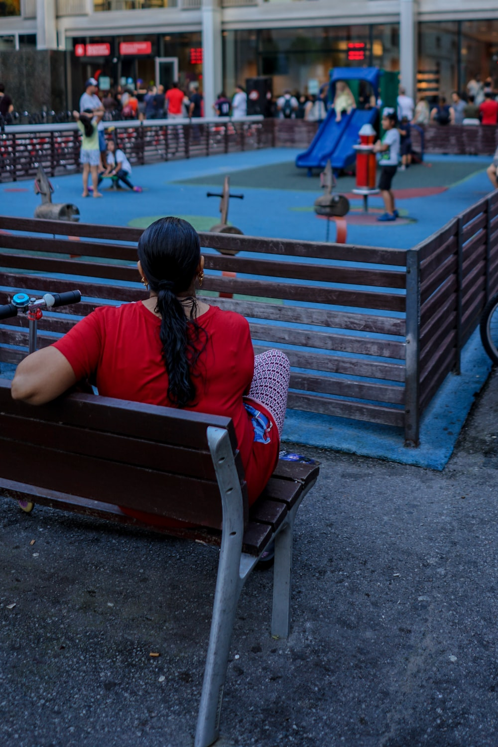woman in red top sitting on bench