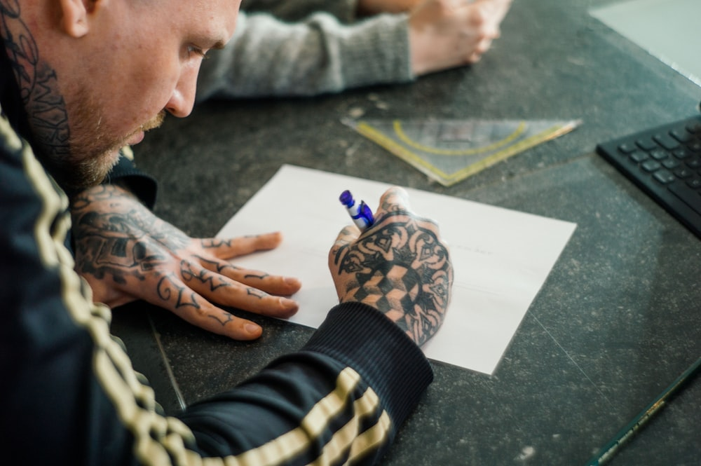 man with tattoos holding blue pen