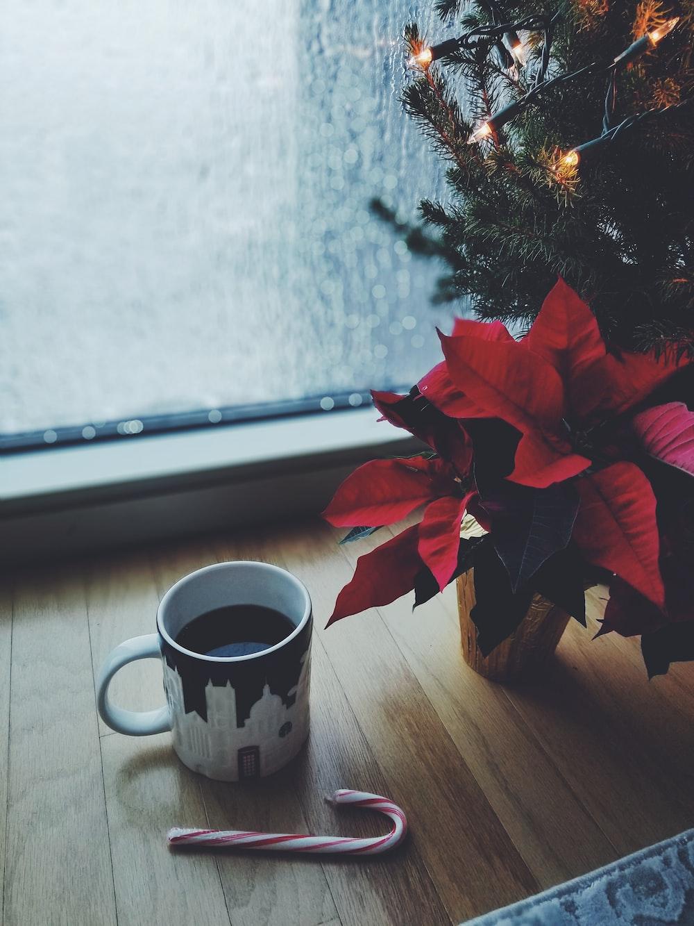 mug of coffee beside christmass tree by the window