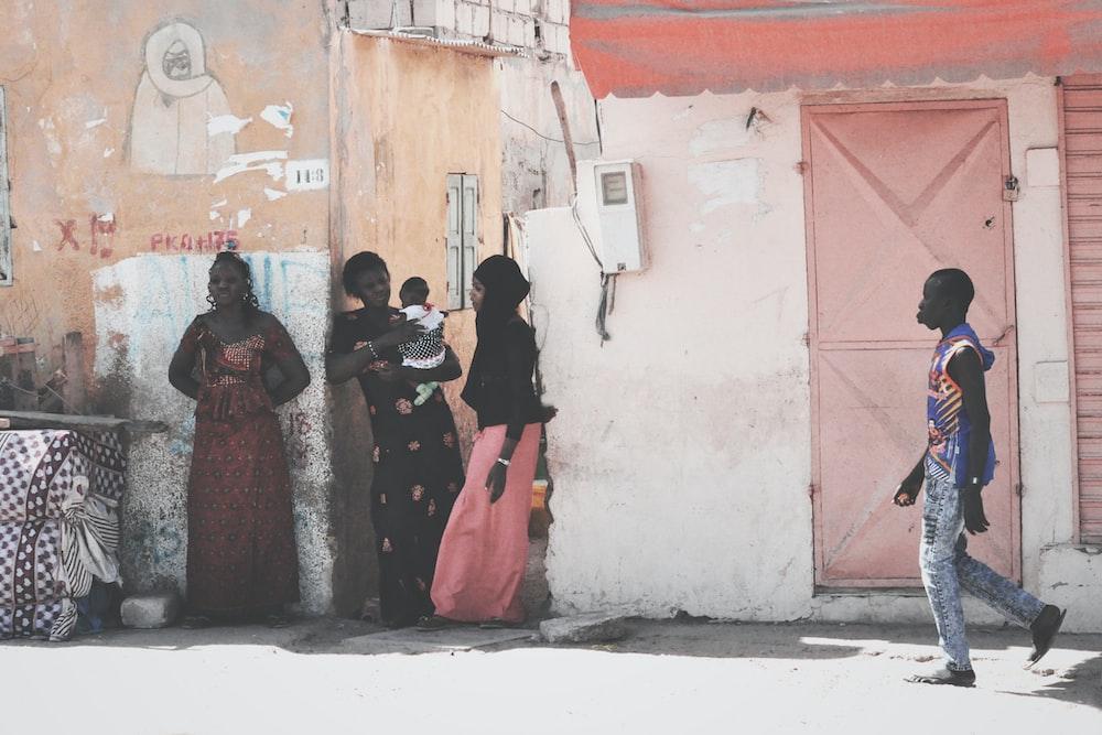 women standing beside white concrete wall