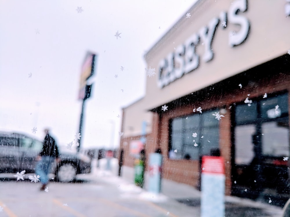 man walking to the car in front of Casey's building during daytime