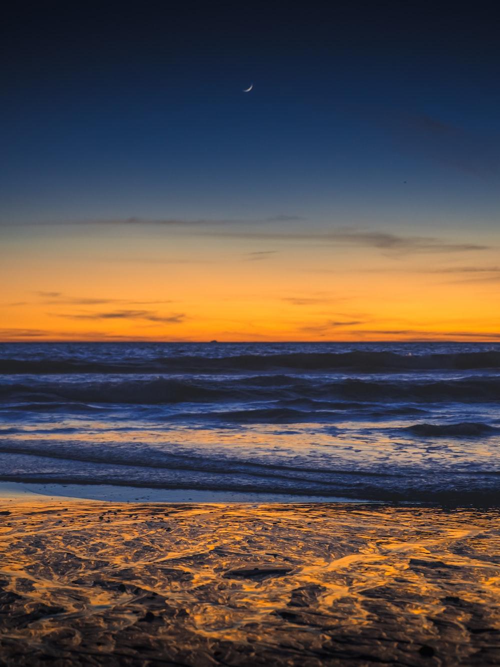 beach under blue sky during golden hour