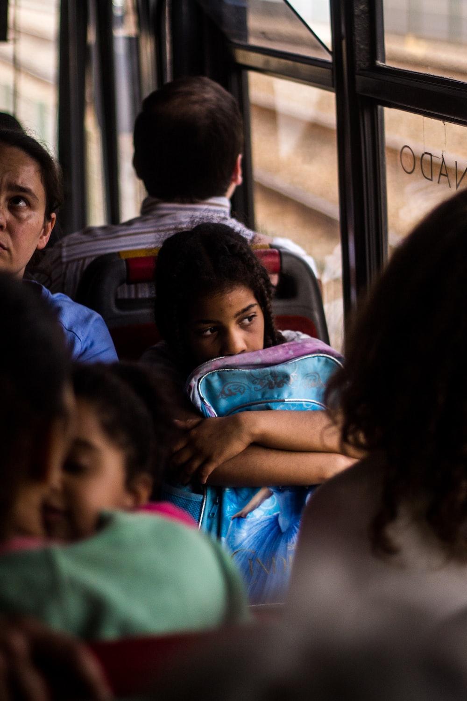 girl with blue bag inside bus